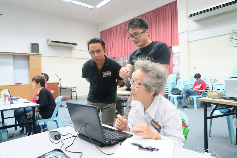 Facilitators guide one of the participants during the workshop.